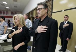 Texas Gov. Rick Perry stands during the national anthem at a meeting with local party activists, Saturday, July 19, 2014, in Algona, Iowa.