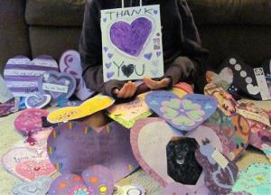 In this June 19, 2014, photo the 12-year-old Waukesha, Wis., victim of the Slender Man attacks holds a Thank You poster for the many supporters from around the world that have sent her cards.
