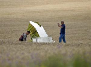 Malaysian air crash investigators take pictures of wreckage at the crash site of Malaysia Airlines Flight 17 near the village of Hrabove, eastern Ukraine, Tuesday, July 22, 2014.