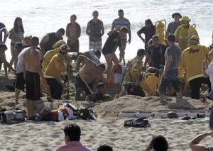 Emergency crew workers and volunteers working to rescue a man at Francis State Beach in Half Moon Bay, Calif.