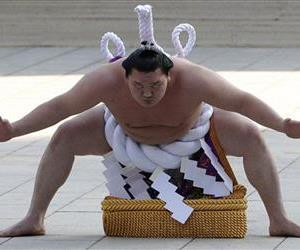 Sumo grand champion Hakuho of Mongolia performs his ring entry forms to dedicate to the Meiji Shrine in Tokyo Friday, Jan. 6, 2012.