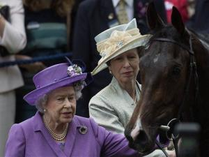In this June 20, 2013 file photo, Queen Elizabeth II and her daughter Princess Anne greet the queen's horse Estimate, who won the Gold Cup horse race.