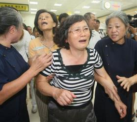 A relative of a passenger on TransAsia Airways flight GE222 that crashed on Penghu reacts at the flight's departure airport in Kaohsiung, Taiwan, Wednesday, July 23, 2014.