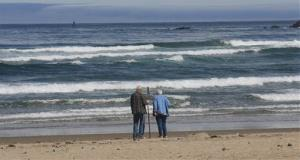 A couple walks along Bastendorff Beach near Charleston, Ore.