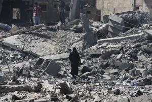 Palestinians walk by the rubble of houses destroyed by Israeli strikes Saturday.