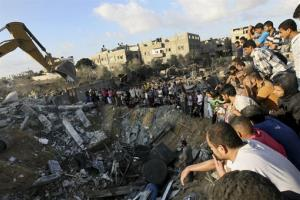 Palestinians gather around the rubble of a building where at least 20 members of the Al Najar extended family were killed by an Israeli strike in Khan Younis, southern Gaza Strip, July 26, 2014.