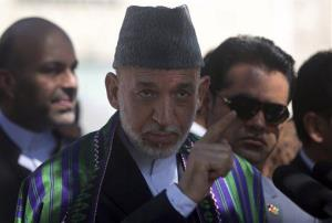 Afghanistan's president Hamid Karzai, center, talks to the media representatives after Eid al-Fitr prayer at the presidential palace in Kabul, Afghanistan, Monday, July 28, 2014.