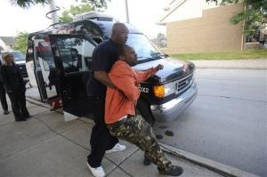 Jamre Pearson is held back by a friend outside his home after his 8-year-old son was hit by a bullet fired from outside.
