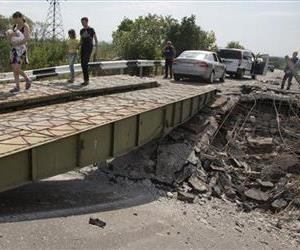 People walk across an exploded bridge near the village of Debaltseve, Donetsk region, eastern Ukraine, Thursday, July 31, 2014.
