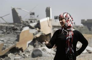 A Palestinian woman stands near the rubble of destroyed houses in Beit Hanoun, Gaza, Friday.