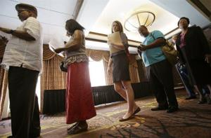 In this Thursday, June 12, 2014 photo, people wait in line for the Cleveland Career Fair in Independence, Ohio.