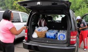 Aundrea Simmons stands next to her minivan with cases of bottled water in Toledo.