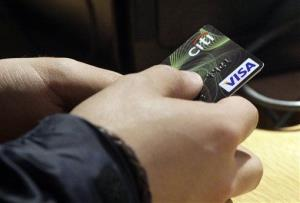In this May 9, 2012 file photo, a Visa credit card is tendered in New York.