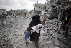 A Palestinian woman passes by rescuers inspecting the rubble of destroyed houses following Israeli strikes in Rafah refugee camp, southern Gaza Strip, Monday, Aug. 4, 2014.