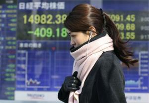 A woman walks by an electronic stock board of a securities firm in Tokyo, Monday, Jan. 27, 2014.