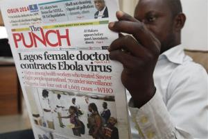 A man reads a newspaper with a headline about a doctor contracting Ebola, in Lagos, Nigeria, Aug. 5, 2014.