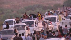 This image made from video taken on Aug. 3, 2014 shows Iraqis people from the Yazidi community arriving in Irbil in northern Iraq after Islamic militants attacked the towns of Sinjar and Zunmar.
