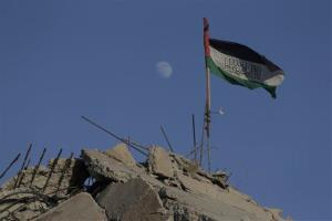 A Palestinian flag flies on the rubble of a house destroyed by an Israeli strike in the Gaza City neighborhood of Shijaiyah.