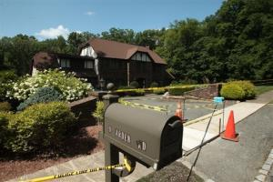 In this Thursday, Aug. 7, 2014 photo, police tape lines the scene at a home in Denville, NJ, where authorities were investigating the deaths of John Bramhall and Joan Bramhall.