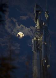 The supermoon rises through the clouds behind the Motherland statue, part of the WWII memorial complex, in Kiev, Ukraine, Sunday, Aug. 10, 2014.