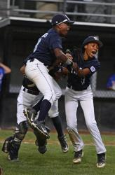 Taney's Jahli Hendricks, left, Scott Bandura, in the background,  and Mo'ne Davis, right, leap for joy.