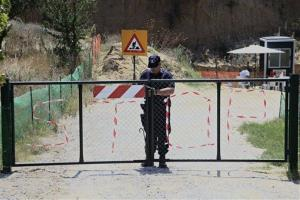 A policeman locks the entrance to a site that archaeologists are excavating at an ancient mound in Amphipolis in northern Greece yesterday.