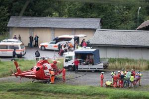 Rescue forces recover a victim of today's train crash, right, near Tiefencastel, Switzerland, Wednesday, Aug.13, 2014.