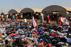 Displaced Iraqis from the Yazidi community look for clothes to wear among items provided by a charity organization at the Nowruz camp, in Derike, Syria, Tuesday.