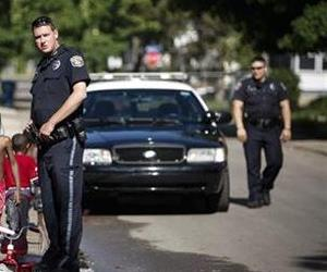 Kalamazoo Public Safety Officer Jason Gates, center, and Officer Joe Hutson, far right, stop on Hays Park Avenue in the Edison neighborhood, Friday, June 6, 2014 in Kalamazoo, Mich.