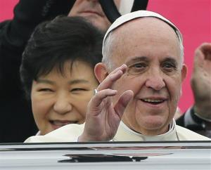 Pope Francis waves upon his arrival at Seoul Air Base as South Korean President Park Geun-hye, left, smiles in Seongnam, South Korea.