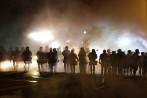 Police advance through smoke on Wednesday, Aug. 13, 2014, in Ferguson, Mo.