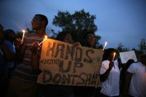 Demonstrators hold candles and signs Thursday in Ferguson, Mo.