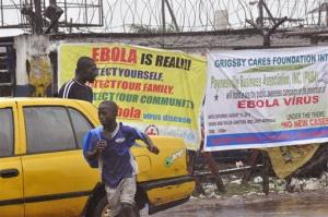 People pass by Ebola virus health warning signs, in the city of Monrovia, Liberia, Sunday, Aug. 17, 2014.
