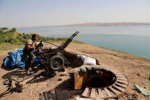 A Kurdish peshmerga fighter prepares his weapon at his combat position near the Mosul Dam at the town of Chamibarakat outside Mosul, Iraq, Sunday, Aug 17, 2014.