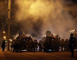 Police wait to advance after tear gas was used to disperse a crowd in Ferguson yesterday.