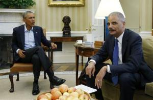 President Barack Obama speaks with Attorney General Eric Holder as news photographers photograph their meeting regarding the fatal police shooting of Michael Brown in Ferguson, Missouri, Monday, Aug. 18, 2014, during their meeting in the Oval Office at the White House in Washington.