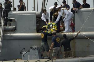 Military officers and a US diplomat pass a wreath to sailors assigned to the Mobile Diving Salvage Unit near Java, Indonesia.