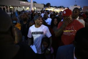 Rapper Nelly, center, walks the streets with protesters in Ferguson yesterday.