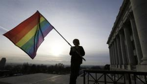 In this Jan. 28, 2014, file photo, Corbin Aoyagi, a supporter of gay marriage, waves a rainbow flag during a rally at the Utah State Capitol in Salt Lake City.