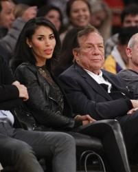LDonald Sterling and V. Stiviano watch the Clippers play the Los Angeles Lakers during an NBA preseason basketball game in Los Angeles on Monday, Dec. 19, 2010.