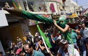 A Palestinian boy holds a representation of a rocket as supporters of Hamas chant slogans against the Israeli military action in Gaza, Friday, Aug. 22, 2014.