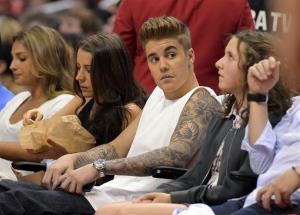This May 11, 2014 file photo shows Justin Bieber watching the Los Angeles Clippers play the Oklahoma City Thunder with his mother Pattie Mallette, second from left, in Los Angeles.