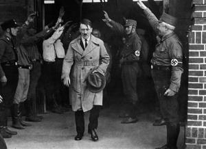 In this Dec. 5, 1931, file photo, Adolf Hitler, leader of the National Socialists, is saluted as he leaves the party's Munich headquarters.