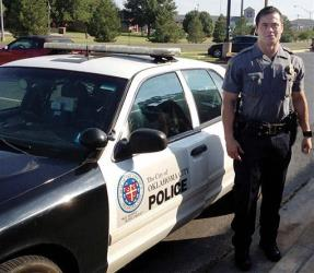 In this Sept. 2, 2012 file photo, provided by the Oklahoma Police Dept., Oklahoma City police officer Daniel Holtzclaw stands next to his vehicle.