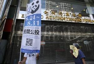 A woman walks past a volunteer with a banner promoting an informal civil referendum in a Macau street yesterday.