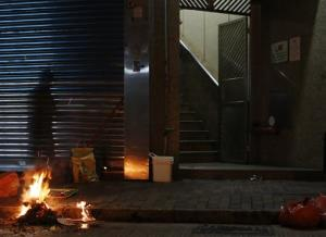 A shadow of a woman is cast near a stair as she burns paper money or locally known as Hell Money, during the Hungry Ghost Festival in Hong Kong.