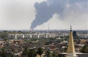 Black smoke billows over the skyline as a fire at the oil depot for the airport rages out of control after being struck in the crossfire of warring militias in Tripoli, Libya Monday, July 28, 2014.