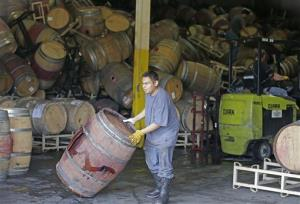A worker removes an earthquake-damaged wine barrel from a barrel storage facility in Napa, Calif.