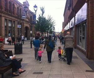 People walk in the town centre, in Rotherham, England, Wednesday, Aug. 27, 2014.