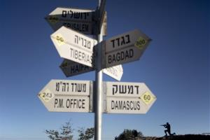 A sign showing the direction and distance to cities stands as a metal board in the shape of a gunman at an observation point in Golan Heights, overlooking the border with Syria, on Aug. 28, 2014.